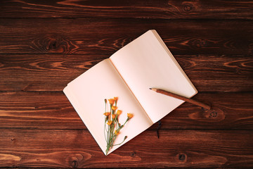 Open notebook, wooden pencil and dandelion on wooden background