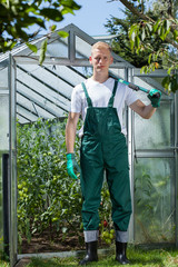 Garden worker standing in front of glasshouse