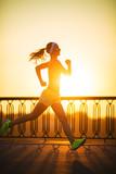 Fototapeta Running woman. Runner is jogging on sunrise outdoors