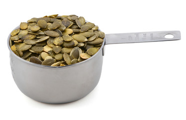 Green pumpkin seeds in a cup measure