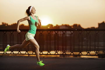 Running woman. Athletic fitness model is jogging on sunrise