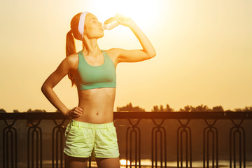 Athletic beautiful woman is drinking pure water from the bottle