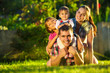 Happy young family having fun outdoors in summer garden - 70771522