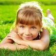 Cute smiling little girl lying on a green grass in the park