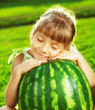 Happy little girl is hugging huge watermelon in summer