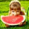 Cute little girl eating watermelon lying on green grass