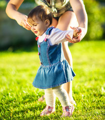 Baby girl is doing her first steps with mothers help outdoors