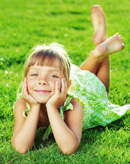 Cute smiling little girl lying on a green grass in the garden