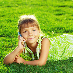 Beautiful little girl is talking on a phone lying on a grass