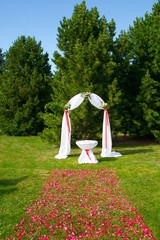 arch with white chiffon and flowers ready for wedding ceremony