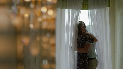 Man and his wife embracing near a window at home