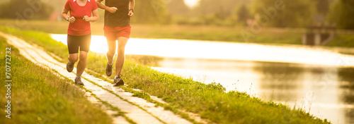 Couple running outdoors, at sunset, by a river - 70772732
