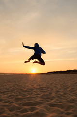 Man silhouette. Jumping in the beach at sunset