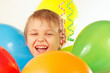 Young smiling boy with festive balloons and a streamer