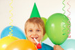 Little blonde boy with whistle and festive balloons