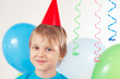 Little boy in festive cap with holiday balls and streamer