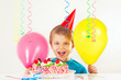 Little smiling boy in cap with birthday cake and balloons