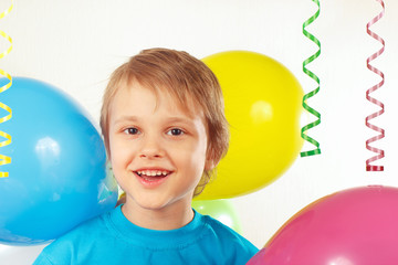 Little boy with festive balloons and a streamer