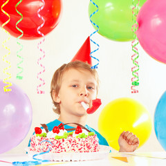 Little boy with birthday cake with whistle and holiday balloons