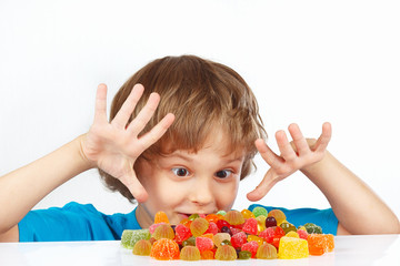 Little boy with colored jelly candies on a white background