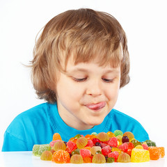 Little child looking at colored jelly candies
