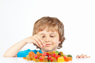 Little blonde boy with candies on a white background