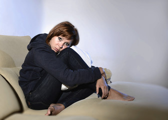 woman sitting on couch holding legs in depression