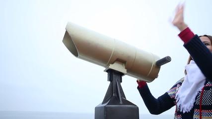 Woman looking through binoculars waving. Full HD with motorized