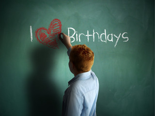 I love Birthdays. Schoolboy writing on a chalkboard.