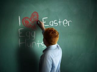 I love Easter Egg Hunts. Schoolboy writing on a chalkboard.