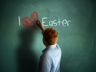 I love Easter. Schoolboy writing on a chalkboard.
