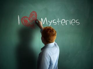 I love Mysteries. Schoolboy writing on a chalkboard.