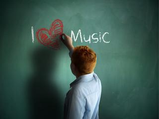 I love Music. Schoolboy writing on a chalkboard.