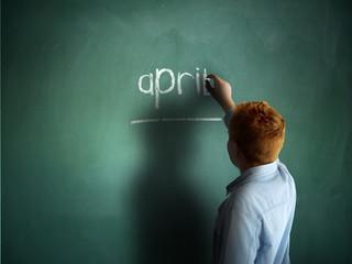 April. Schoolboy writing on a chalkboard.