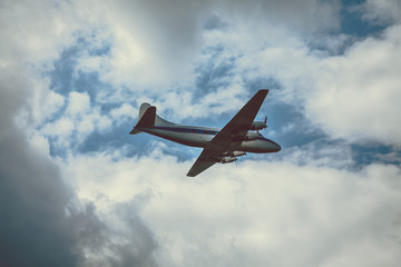 Old passenger plane on cloudy sky