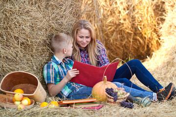 Мама и сын читают книгу на сеновале