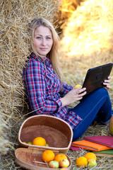 Девушка с планшетом и фруктами отдыхает на сеновале