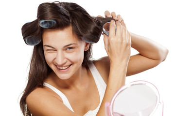 young smiling woman putting curlers in her hair