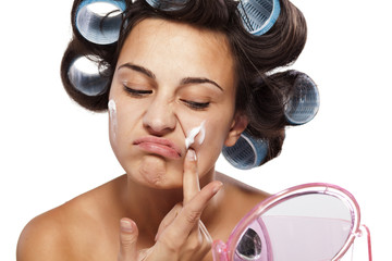 frowning and unsatisfied woman with curlers applied face cream