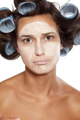 sad woman with curlers posing with poorly chosen foundation