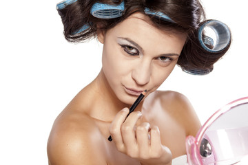 woman with curlers posing with eyeliner