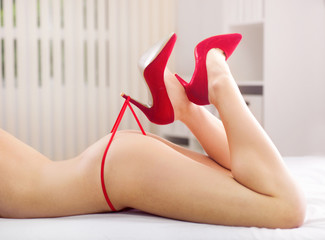 Beautiful woman's legs in heels playing with red panties