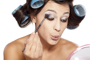 woman with curlers apply eye shadow