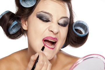 Funny woman with curlers and bad makeup applied lip pencil