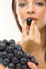 young beautiful woman eating grapes