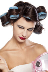funny woman with curlers and bad makeup winking
