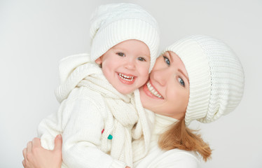 happy family: mother and baby daughter in white winter hats