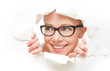 woman in glasses peeking through  hole torn in paper