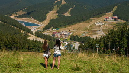 Beautiful young girls on mountain looking at the mountains