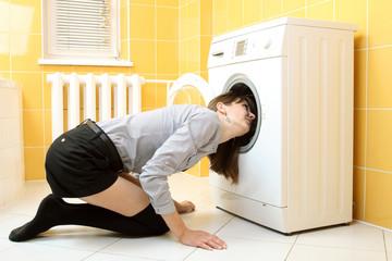 Ordinary simple beautiful girl near a washing machine